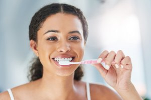 young woman brushing teeth with manual toothbrush