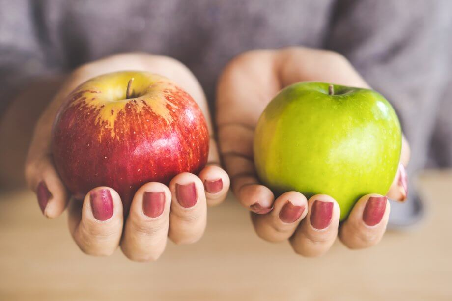 Woman holding a red apple in one hand and a green apple in the other. Only her hands and the apples are visible.