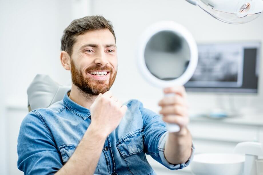 Photograph of a man wearing a blue shirt, smiling while looking at himself in a handheld mirror while at a dentist office.