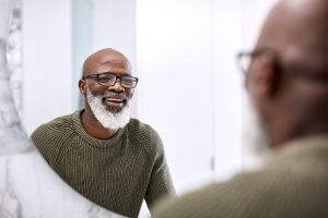 man with beard looking in mirror, smiling