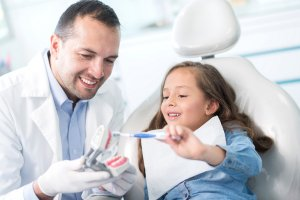 young girl in exam chair with dentist holding model of teeth