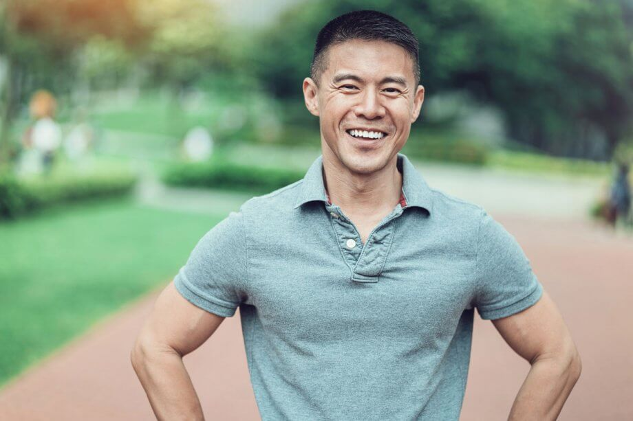 smiling man in grey polo standing outside