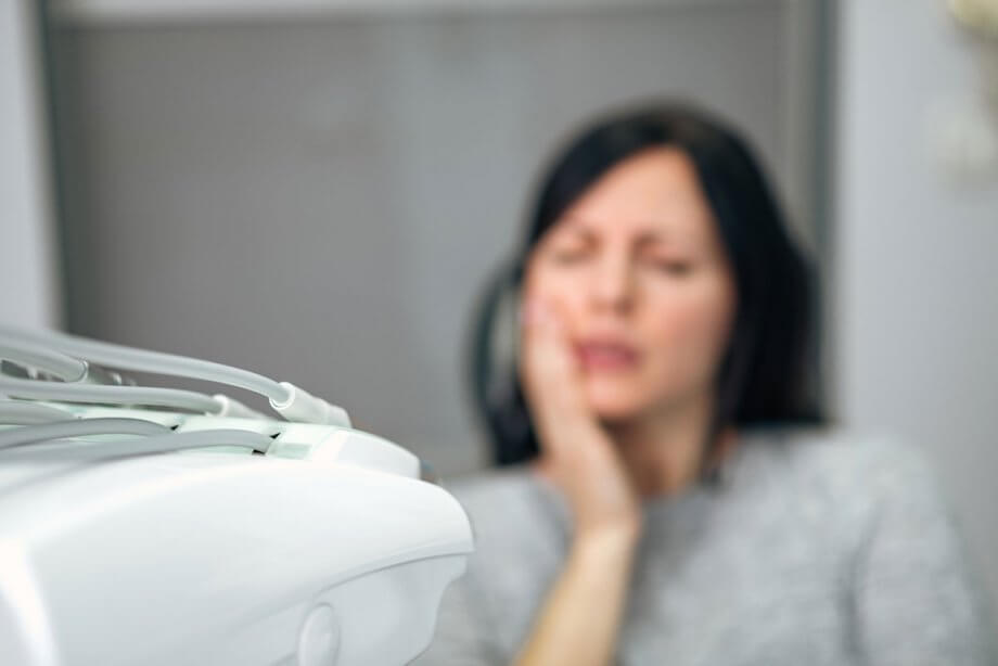 blurry image of woman holding jaw in pain