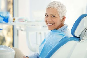 smiling older woman with short grey hair sitting in dental exam chair