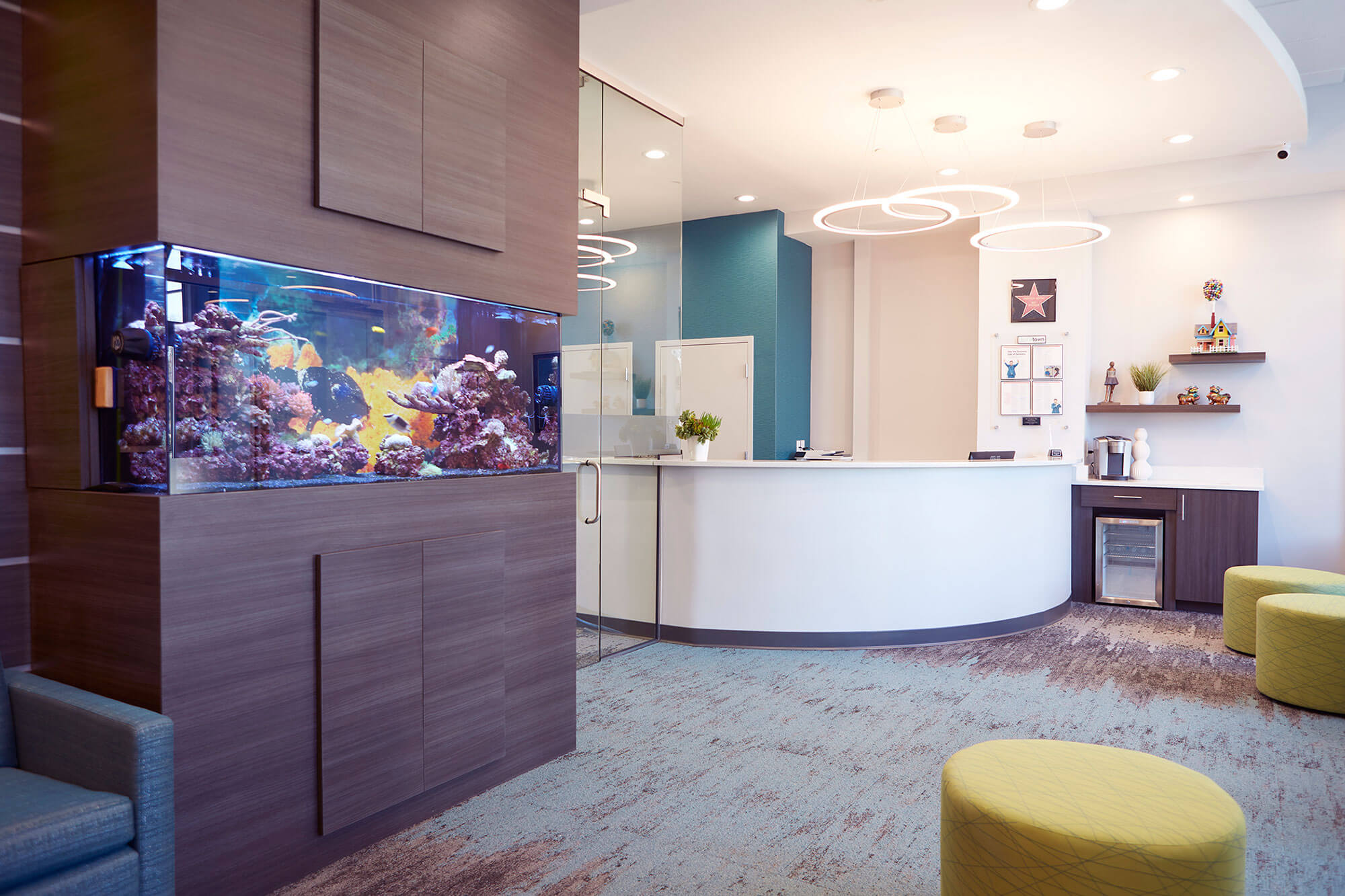 lobby of dental office with fish tank, coffee station and round yellow ottomans