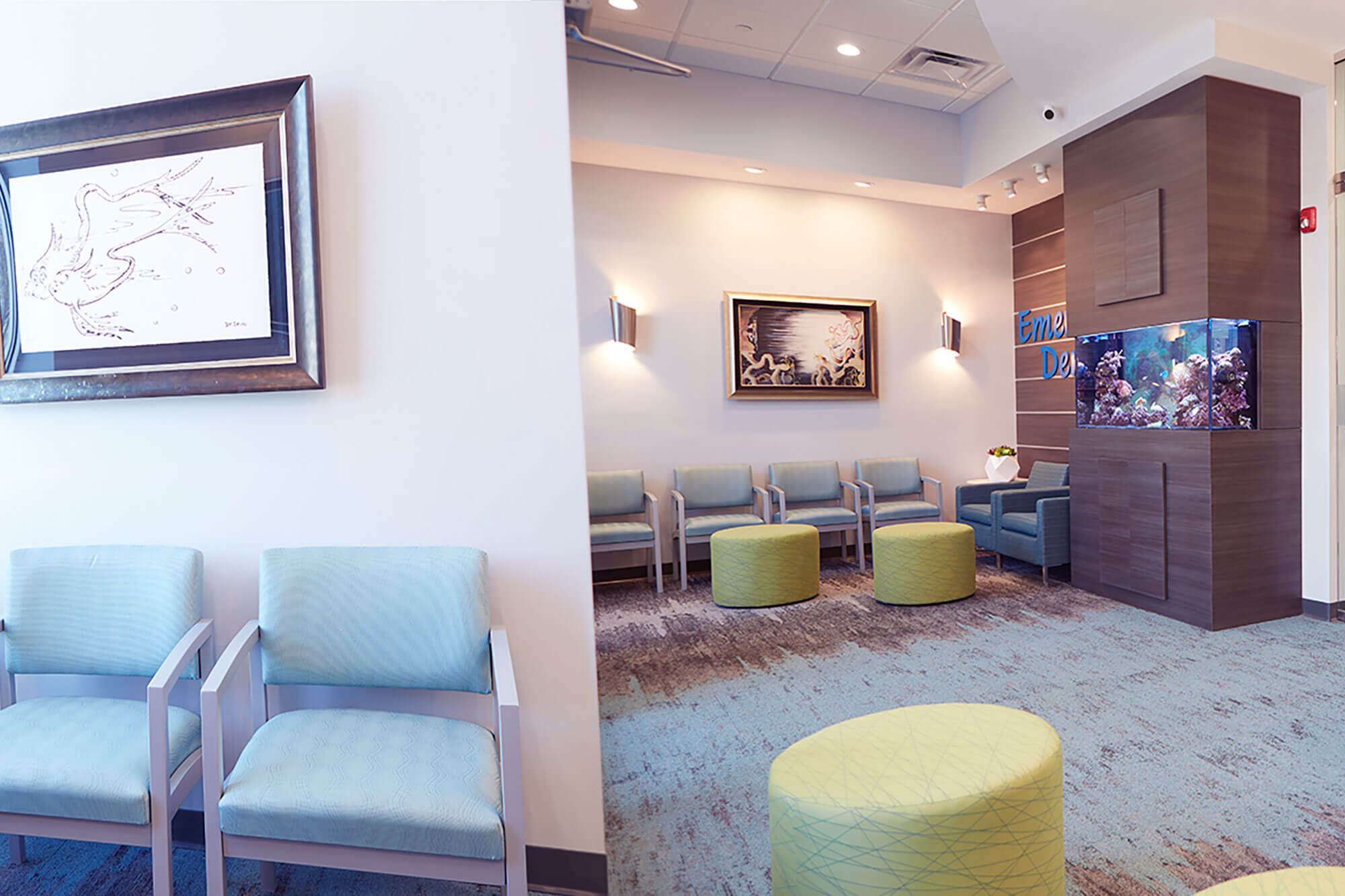 lobby of dental office with fish tank, grey seats and yellow ottomans